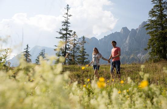 Ein Paar spaziert im Wanderurlaub im Salzkammergut durch die Natur