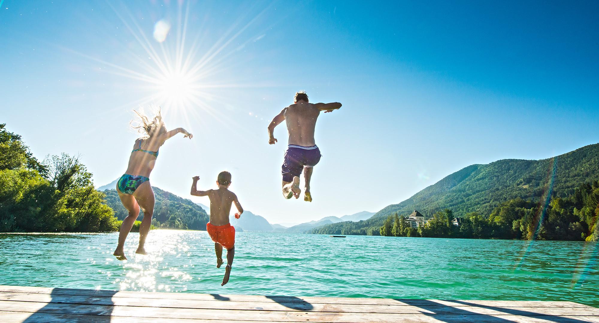 Eine Familie spring beim Badeurlaub im Salzkammergut in den See