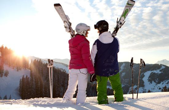 Ein Paar mit Skiausrüstung beim Skiurlaub im Salzkammergut