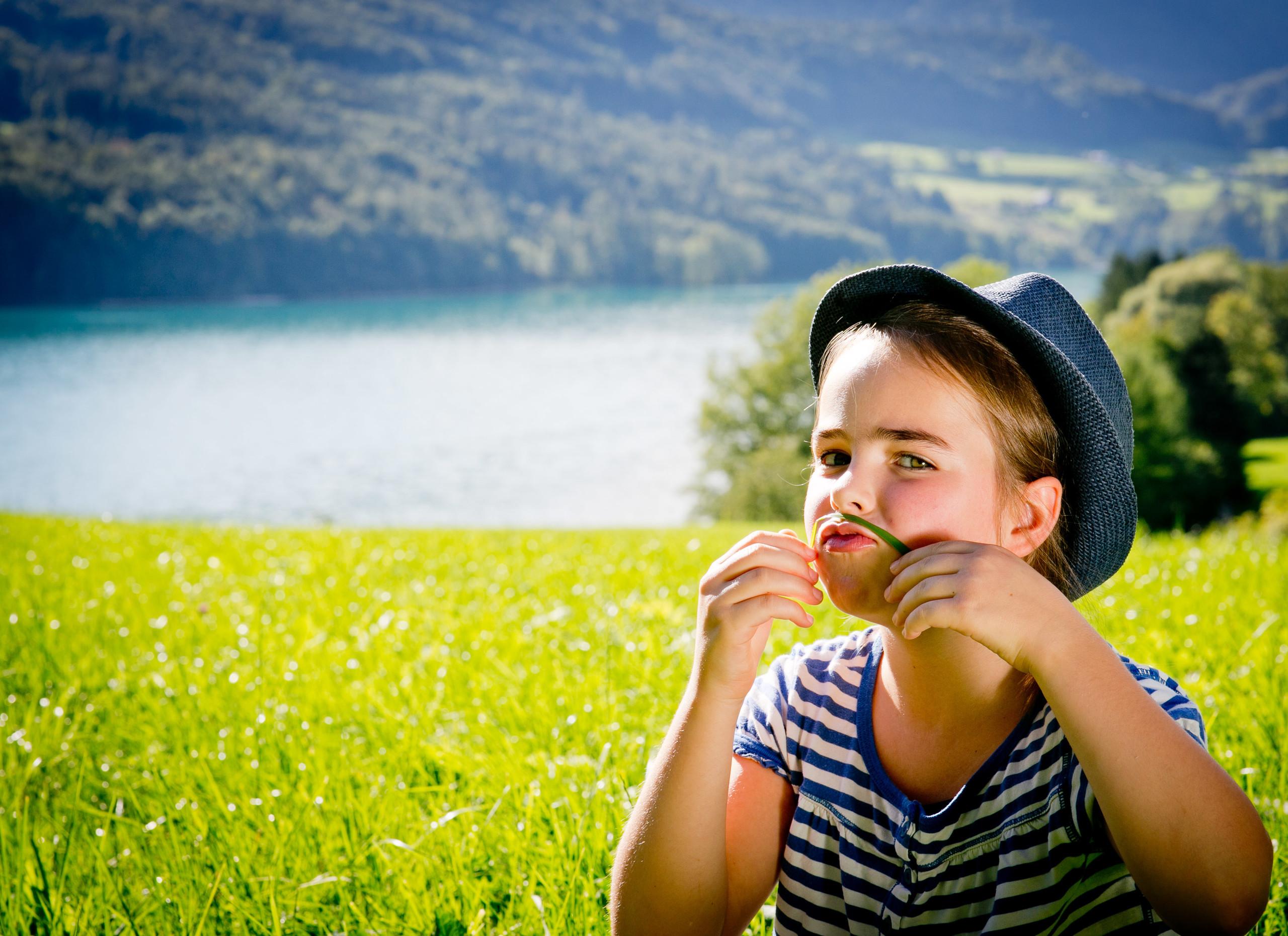 Ein Mädchen spielt auf einer Wiese im Urlaub im Salzburger Land