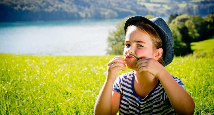 Ein Mädchen spielt im Familienurlaub im Salzkammergut auf einer Wiese