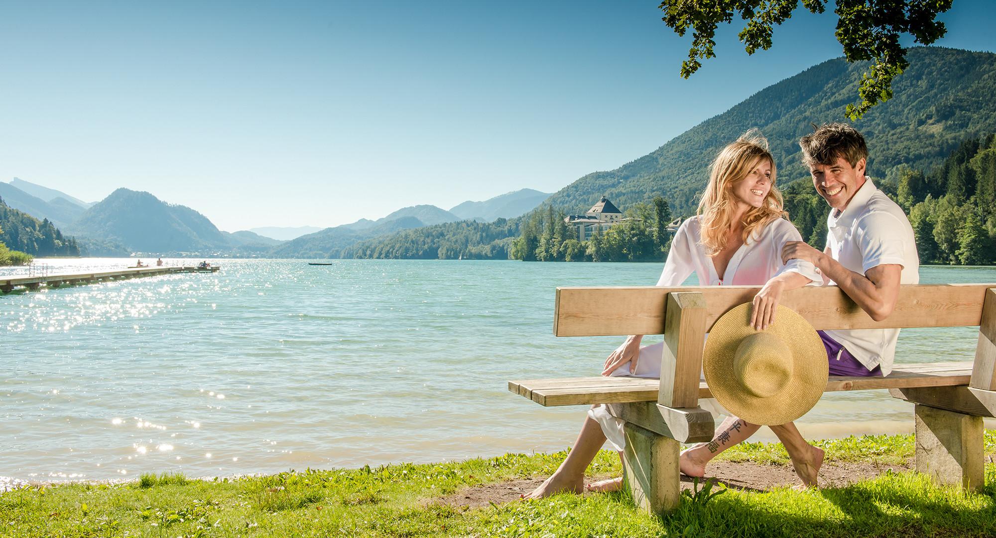 Ein Paar sitzt im Urlaub beim Fuschlsee auf einer Bank am Ufer