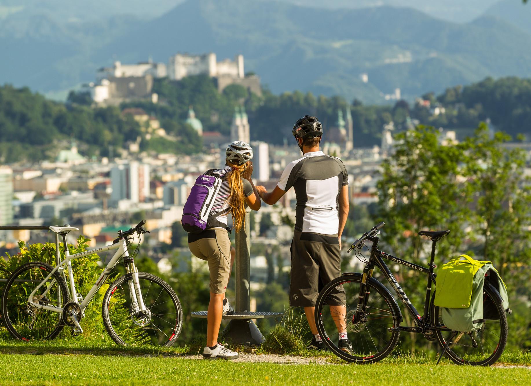 Ein Paar genießt den Ausblick auf die Stadt im Urlaub im Salzburger Land