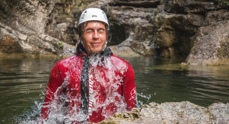 Ein Mann taucht beim Canyoning vom 3* Hotel Obermayr in Salzburg Umgebung aus dem Wasser