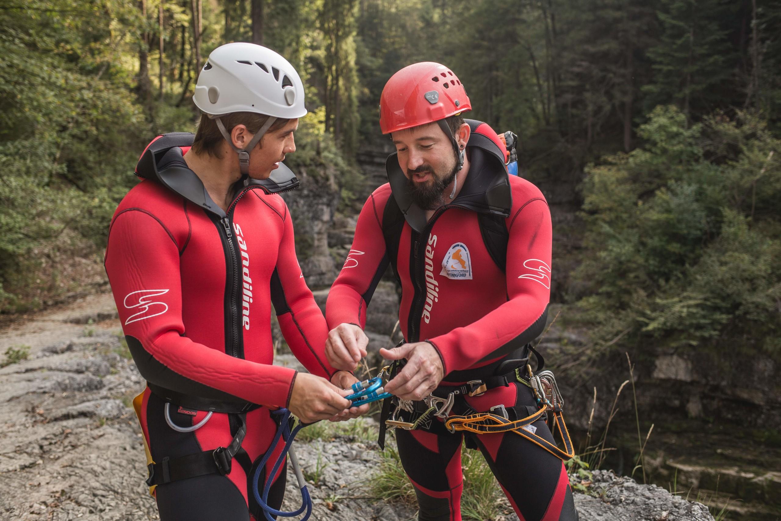 Max Obermayr erklärt einem Mann die Sicherung bei den geführten Canyoning-Touren im Salzkammergut