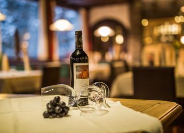 Detailansicht einer Flasche Wein mit Gläsern im Gasthaus Obermayr