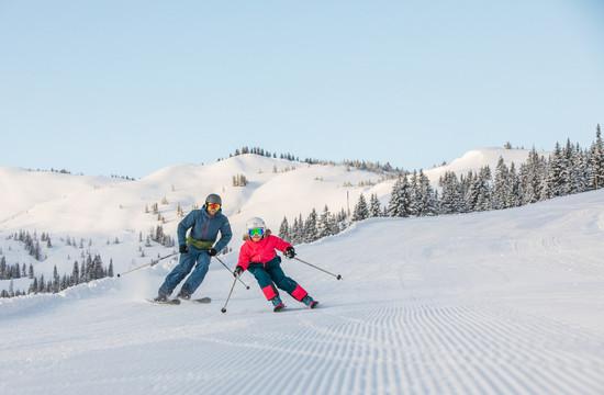 Ein Vater saust beim Skiurlaub im Salzkammergut mit seinem Kind die Piste hinunter