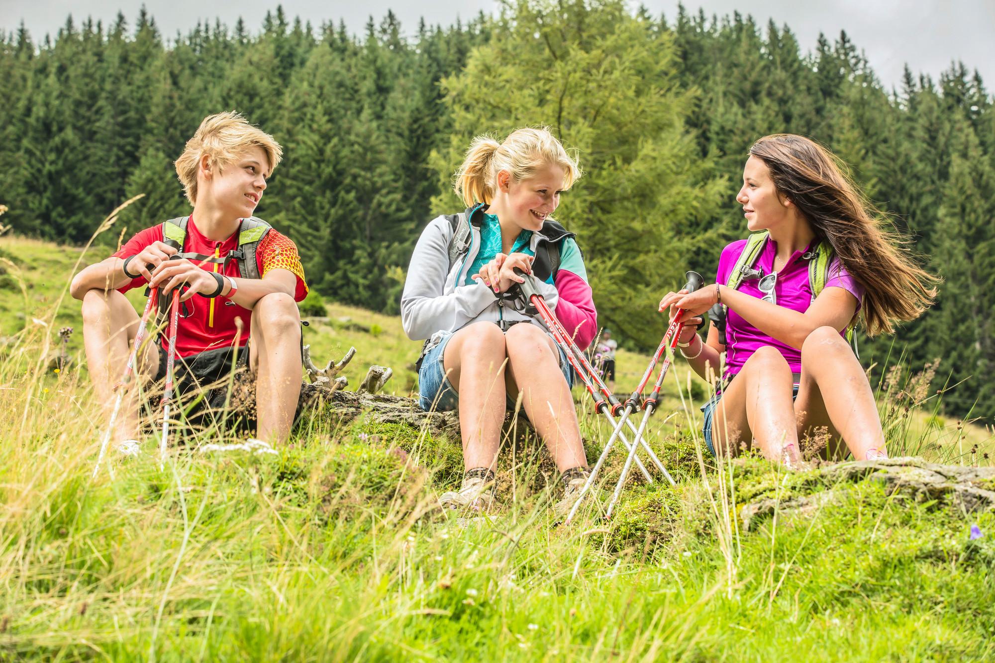Drei Teenager sitzen im Wanderurlaub im Salzkammergut auf einer Bergwiese