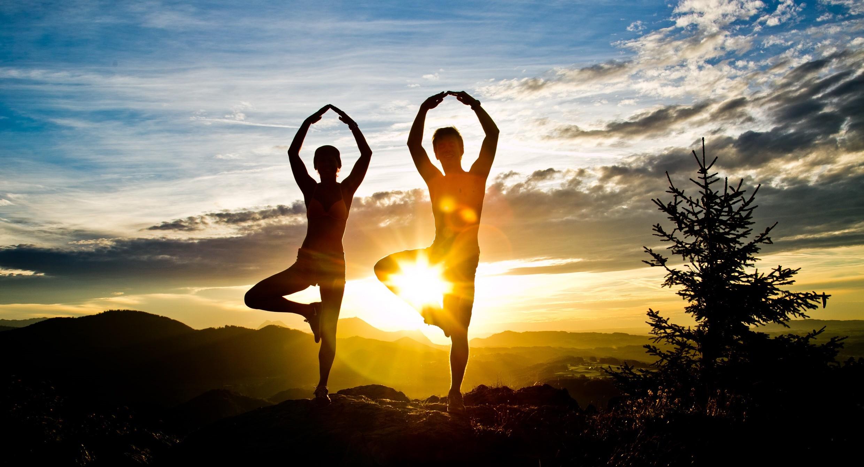 Ein Paar macht im Urlaub im Salzburger Land Yoga bei Sonnenuntergang