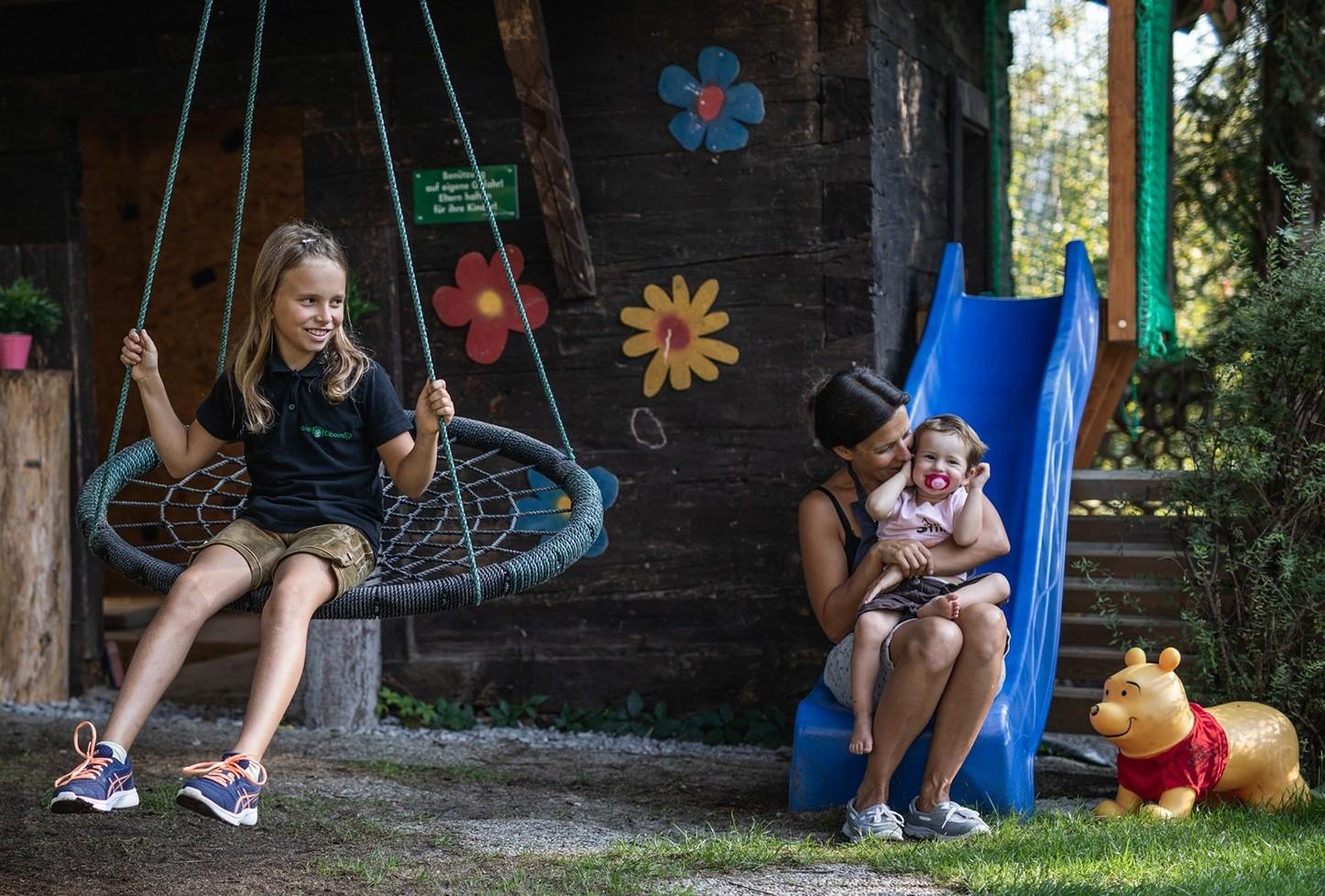 Eine Mutter spielt im Familienurlaub im Salzkammergut mit ihren zwei Töchtern am Spielplatz