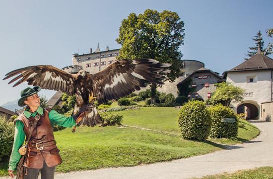 Eine Frau mit einem Falken am Arm vor der Festung Hohenwerfen