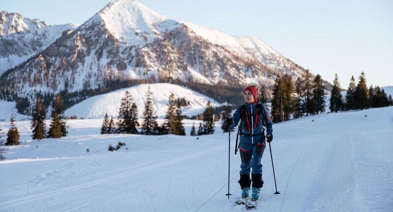 Ein Mann beim Skitouren im Salzkammergut mit seinem Hund