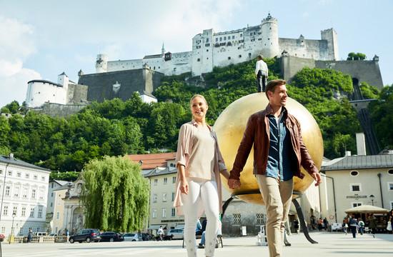 Ein Paar spaziert beim Urlaub in Salzburg durch die Altstadt