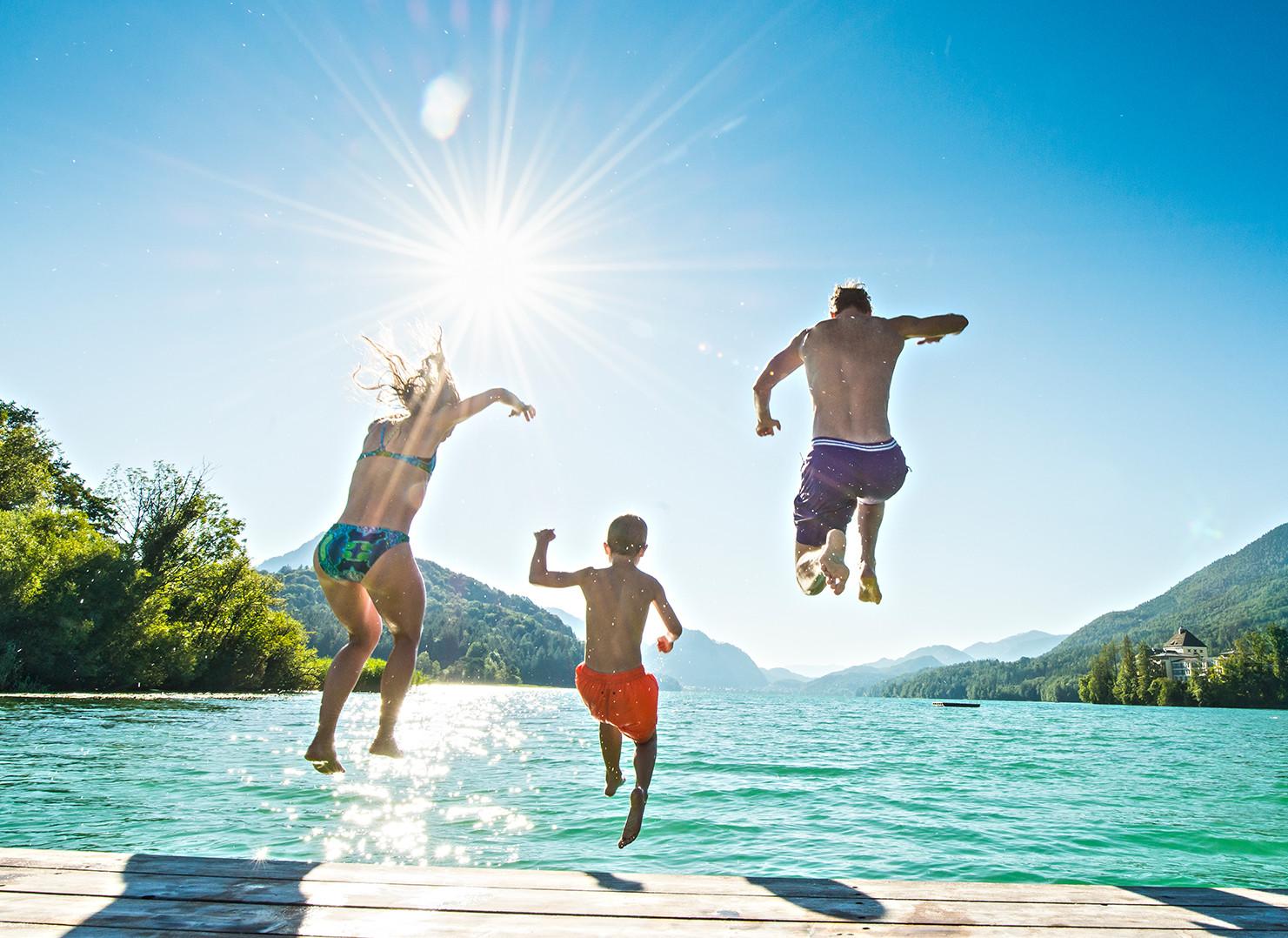 Eine Familie springt im Aktivurlaub im Salzkammergut  in den See