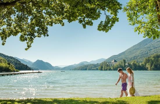 Ein Paar spaziert im Badeurlaub im Salzkammergut an einem See entlang