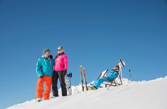 Eine Familie beim Schlittenfahren im Skiurlaub im Salzkammergut