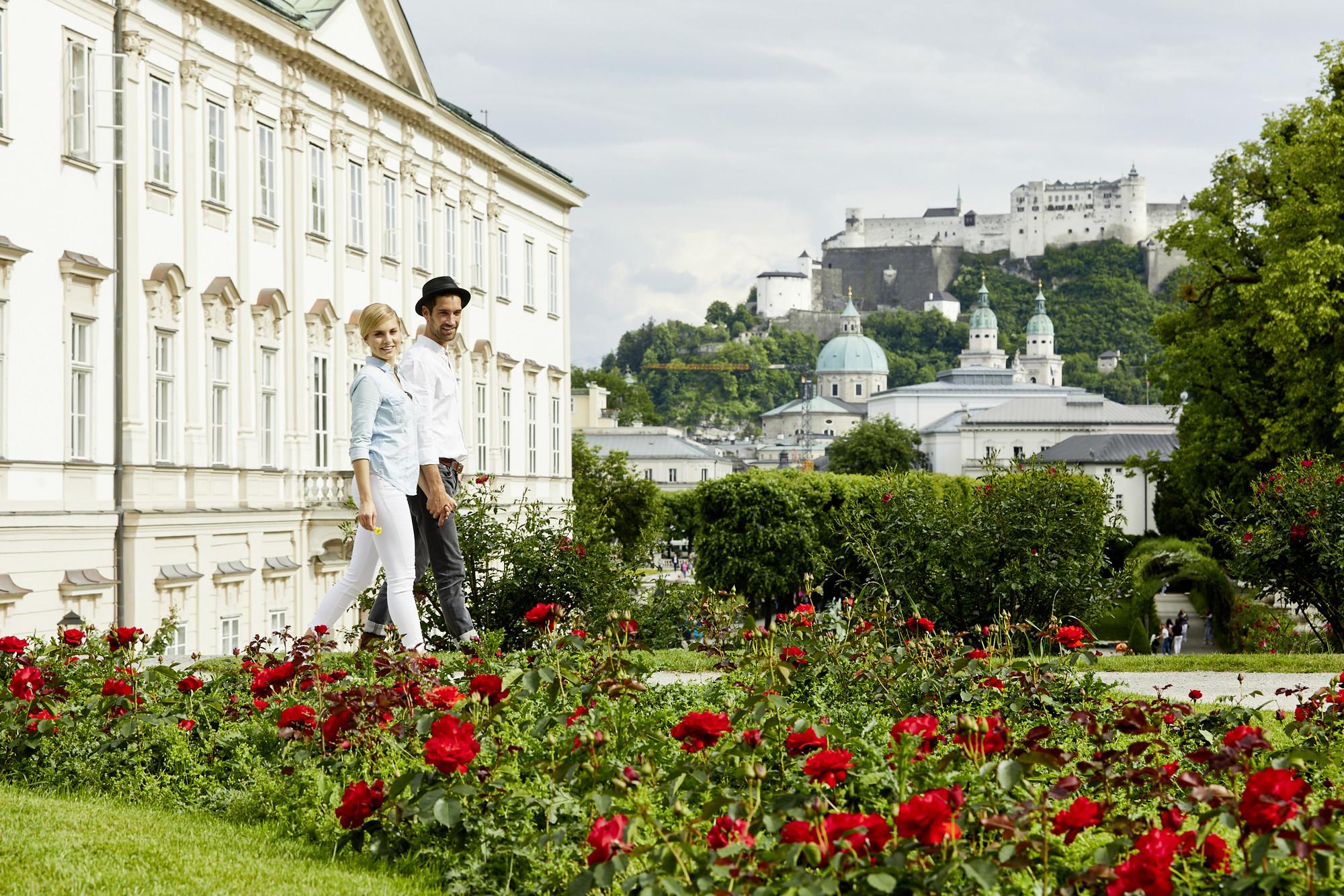 Ein Paar spaziert beim Urlaub in Salzburg durch den Mirabellgarten