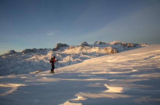 Ein Mann steht beim Skitouren im Salzkammergut in einer verschneiten Landschaft