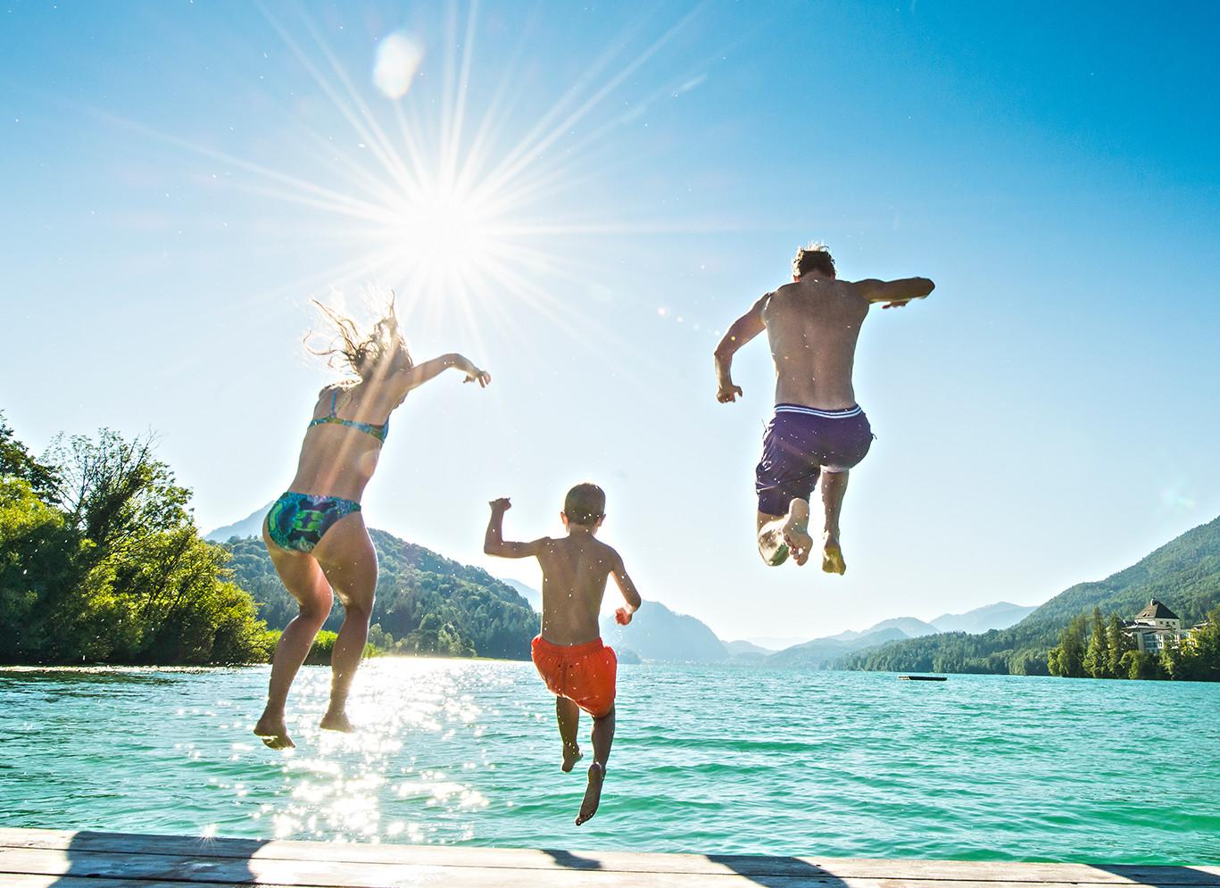 Eine Familie springt im Urlaub beim Fuschlsee in den See