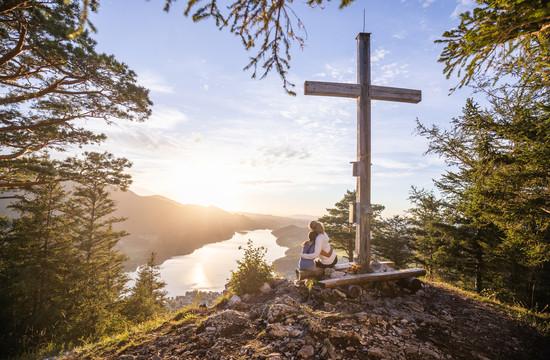Kind und Mutter sitzen beim Gipfelkreuz am Ellmaustein und genießen den Blick auf den Fuschlsee