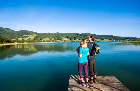 Ein Paar genießt im Badeurlaub im Salzkammergut den Ausblick über den See