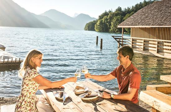 Ein Paar stoßt im Badeurlaub im Salzkammergut mit einem Glas Wein am Seeufer an