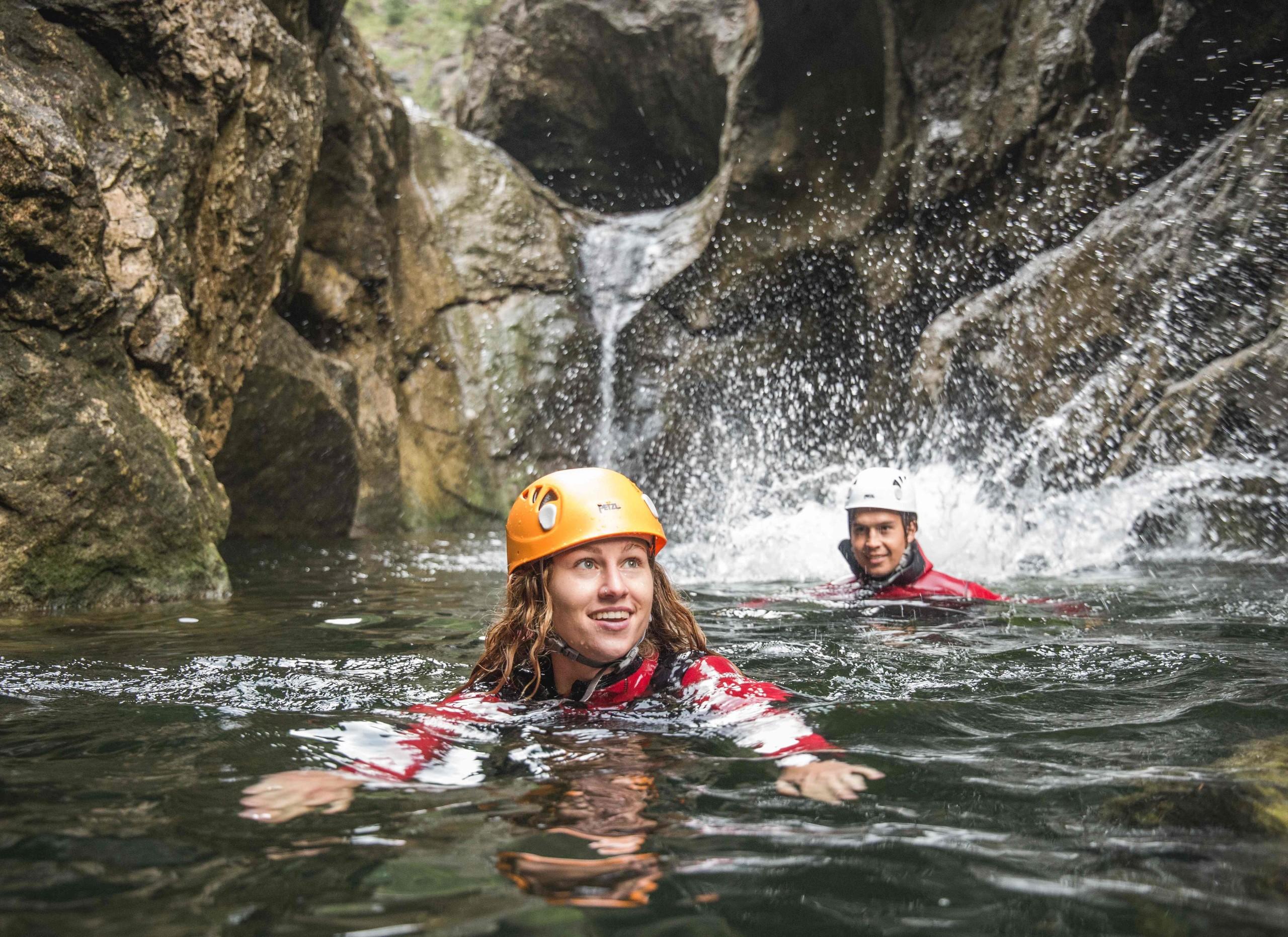 Ein Mann und eine Frau schwimmen beim Canyoning im Aktivurlaub im Salzkammergut durch die Klamm